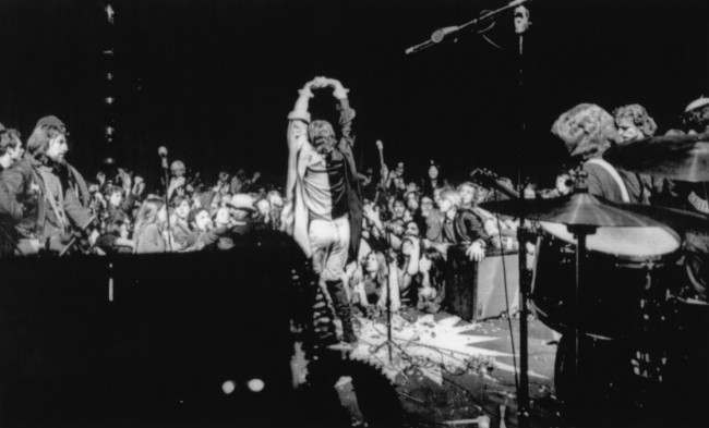 Mick Jagger, center, dances on stage causing audience members to raise their arms and hands during rock concert at the Altamont Speedway near Livermore, Calif., Dec. 9, 1969. Hells Angels flank the stage during the Stones' concert