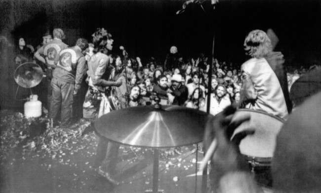 Rolling Stones Keith Richards (left) and Mick Jagger (right) sing on the rose petal-littered stage during free rock concert at Altamont Speedway near Livermore, Calif., Dec. 6, 1969. Hells Angels, far left held back surging crowd. The hand of drummer Charlie Watts is shown in foreground.