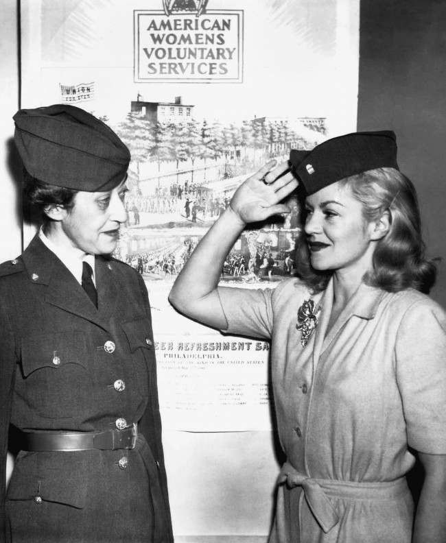 Mrs. Morton S. Stern (left) gets a salute from Claire Trevor after the movie actress had been inducted in the American women's voluntary service in New York, Dec. 18, 1941. (AP Photo/John Rooney)