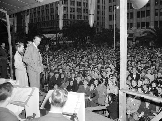 Volunteer salesman Gary Cooper takes time out from work in a new movie to chalk up the highest record for selling Defense Bonds at the Defense House in Pershing Square in Los Angeles, California on Feb. 8, 1942, after making a stirring 15-minute speech, the longest of his public career. Cooper attracted the longest line of purchasers and sold more bonds than any motion picture star since the Defense House was opened, according to the Treasury Department. With him on the platform is lovely Virginia Gilmore of the films. (AP Photo)