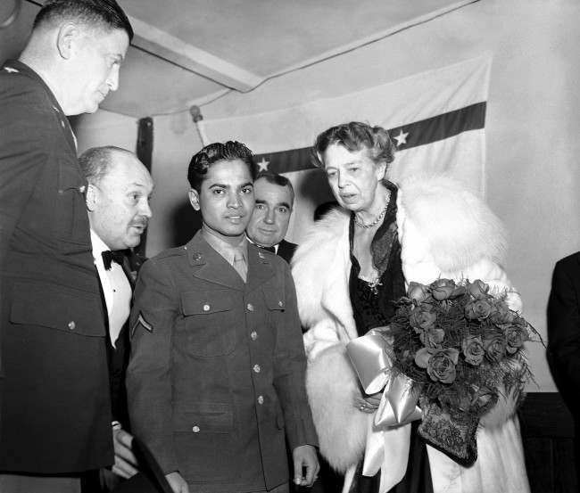 "Eleanor Roosevelt holds a bouquet of roses as she stands with Sabu, the ""Elephant Boy"" of movie fame, and now a soldier attached to Fort Meade, Md., at the president's birthday ball celebration at a USO post in the YMCS in Washington on Jan. 29, 1944. (AP Photo/GBF)"