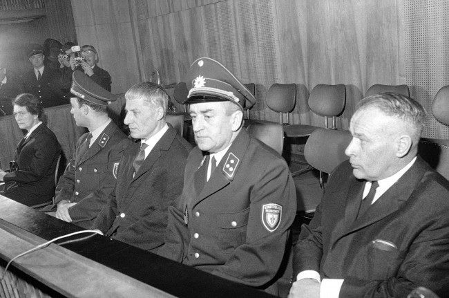 Three former Nazi officials sit with uniformed West German guards as they go on trial in Munich's Palace of Justice on Jan. 23, 1967, on charges of aiding in the mass murder of thousands of Dutch Jews in extermination camps. From right the defendants are, Wilhelm Harster, former major general in the SS Elite Guard, who is 62; Wilhelm Zoepf, 58, former SS major; and Gertrud Slottke, 64, aide to Zoepf. (AP Photo/Klaus Frings)