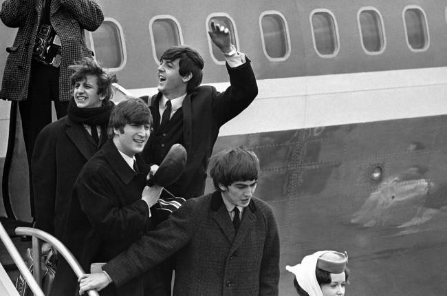 Britain''s Beatles make a windswept arrival in New York on Feb. 7, 1964, as they step down from the plane that brought them from London, at Kennedy airport. From left to right, Ringo Starr, John Lennon, Paul McCartney and George Harrison (AP Photo)
