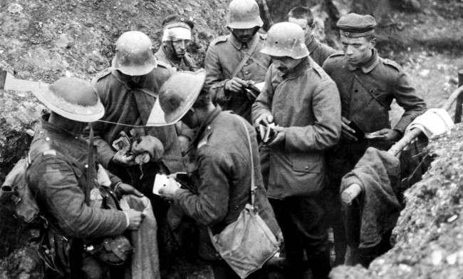 British troops sort through the belongings of German prisoners in a trench.