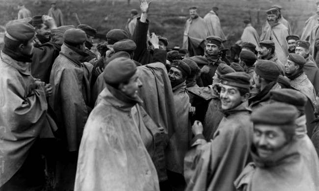 Cheerful German prisoners in forage caps and waterproof capes surround a member of a visiting News Agency in an effort to cadge cigarettes. Western Front, c1918.