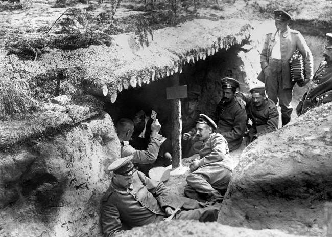 German soldiers of the 12th (2nd Brandenburg) Regiment playing cards in a dugout in a shallow trench in German-occupied Russian Poland during the First World War. One of the soldiers (far right) is holding an accordion.