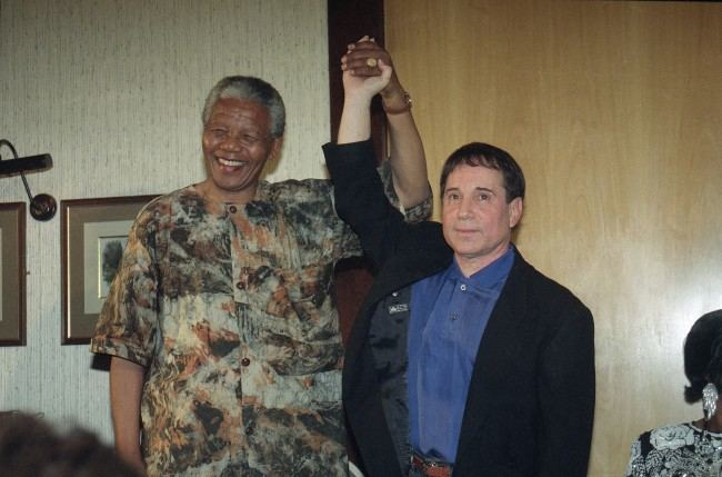 lson Mandela the president of African National Congress claps hands with American singer and songwriter Paul Simon in a gesture that signals the end of the boycott imposed by anti-Apartheid organizations, at a function held in Simon honour in Johannesburg, South Africa Friday, Jan. 10, 1992. (AP Photo/ Adil Bradlow)
