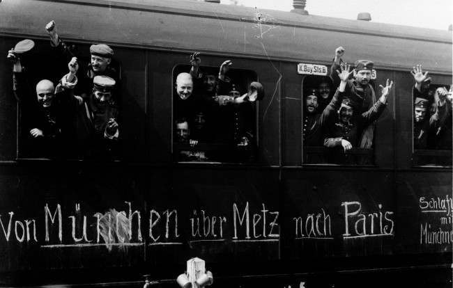 1915: Cheerful Bavarian soldiers of the German Army wave from their troop train as they leave Munich for the Western Front (via Metz) and, they hope, the fall of Paris.