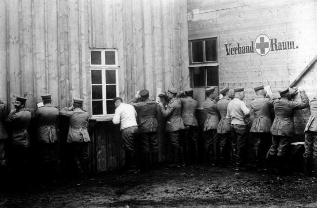c1915: German soldiers, outside a Field Post Office, making use of a wall to write home from the Front.