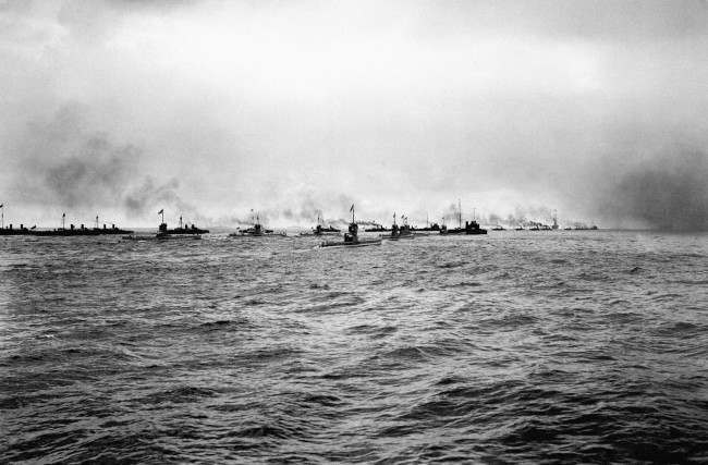 A flotilla of German submarines (U-Boats) and torpedo boats heading out to sea.