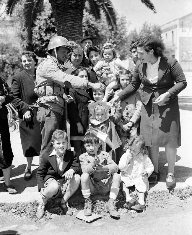 Welcomed to Bizerte by the enthusiastic French women and children, an American soldier hands out candy and chewing gum in return, May 25, 1943. (AP Photo/Herbert K. White)