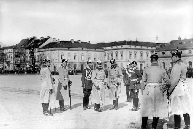 Kaiser Wilhelm II stands with officers as he prepares to inspect a group of gunners who performed well in tests of marksmanship.