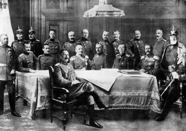 Kaiser Wilhelm II surrounded by his general staff. Standing (from left to right): Bulow, Mackensen, Molkte, Crown Prince Wilhelm, General Francois, Lumenoff, Falkennayn, Einem, Baseler, Chancellor Bathmann Hollweg, Heringen. Seated (from left to right): Crown Prince of Bavaria, Duke Wurtemburg, General Kluck, Emmich, Haeseler, Hindenburg, Admiral Tirpitz.