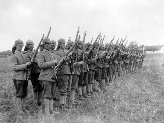 German soldiers wearing their new helmets, which have been modified to remove the spike.