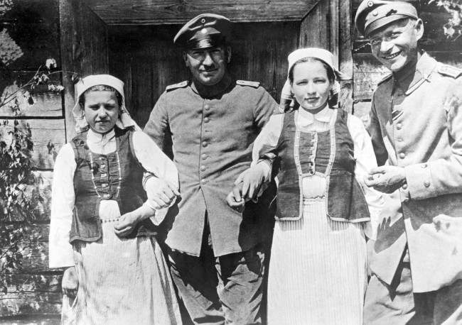 German soldiers arm-in-arm with two Polish girls.