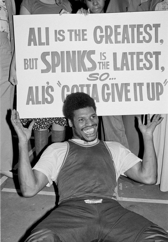 Heavyweight challenger Leon Spinks clowns for the photographers in Las Vegas, Feb. 10, 1978 where he is in training for his title bout against Muhammad Ali, Feb. 15. The sign was provided by some Spinks promoters. (