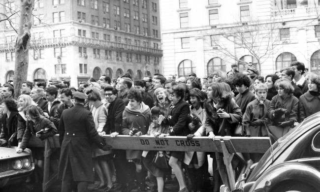 Police enforce the barricades outside New York's Plaza Hotel as fans push forward in hopes of a view of The Beatles after their arrival for an American tour on February 7, 1964. (AP Photo)