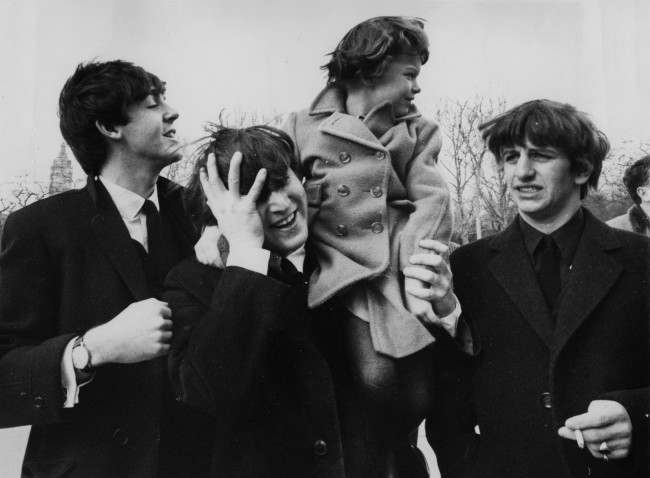 John Lennon, center, holds his forehead as 5-year-old Debbie Fyall, of London, England, sits on his shoulders, in New York, Central Park, USA, February 8, 1964. The other two members of the Beatles are Paul McCartney, left, and Ringo Starr, right. (AP Photo/The Beatles)