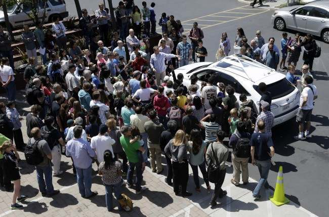 A crowd gathers around Google's self-driving car during a demonstration for employees and their children at Google headquarters in Mountain View, Calif., Thursday, April 25, 2013. (AP Photo/Marcio Jose Sanchez)