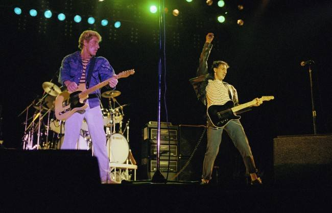 Roger Daltrey watches as Peter Townshend, right, use a windmill motion to strum his guitar during The Who concert in the Seattle Kingdome on Wednesday, Oct. 21, 1982.