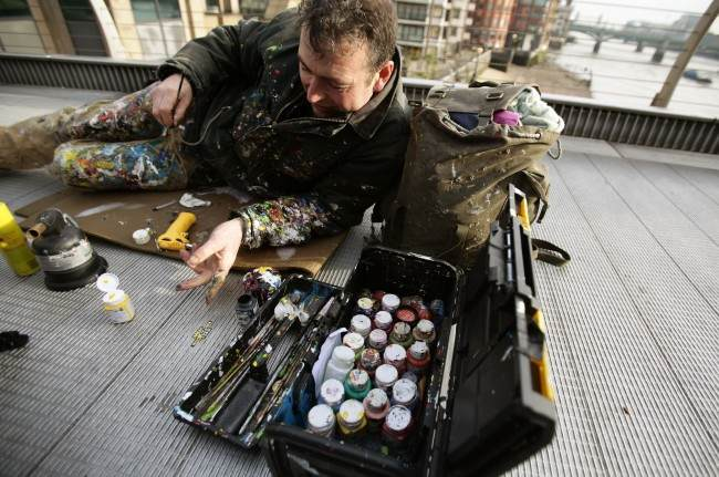 Artist Ben Wilson who paints art on discarded gum, and is also known as 'Chewing Gum Man', at work on the Millennium Bridge in London.