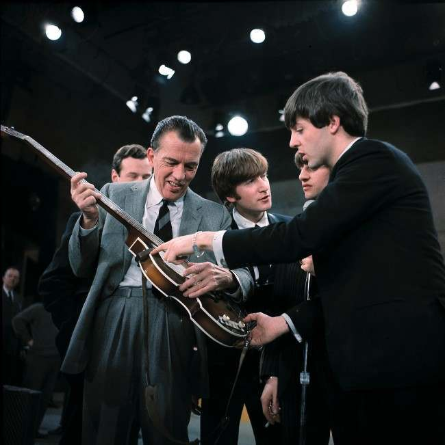 Three of the four member of the British group the Beatles are shown with Ed Sullivan before their live television appearance on The Ed Sullivan Show in New York City, Feb. 10, 1964. From left are, Paul McCartney, Ringo Starr, partial view, George Harrison and Sullivan. (AP Photo)