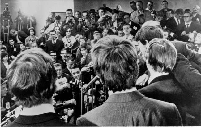 The Beatles face the media on arrival at the John F. Kennedy ariport in New York City. Feb. 7, 1964. The British rock and roll group was also greeted by a screaming crowd estimated at 5,000. (AP Photo/Charles Tasnadi)