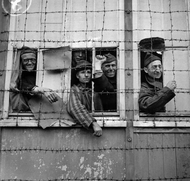 "Prisoners look out from behind a barbed wire enclosure at the Dachau concentration camp in Germany in 1945. Nazi dictator Adolf Hitler organized concentration camps as a ""final solution"" to eliminate European Jewry in his pursuit of the purity of the Aryan race. Auschwitz, Buchenwald and Bergen-Belsen were other camps involved in exterminating over 6,000,000 Jews. The Allied Forces liberated the death camps and their fortunate survivors in 1945. Germany surrendered on May 7, 1945. (AP Photo)"
