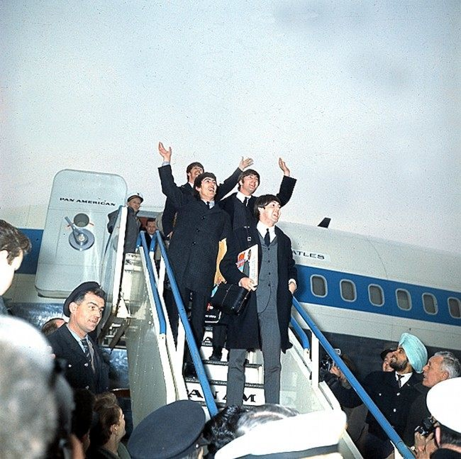 British pop group the Beatles wave as they arrive at London Airport, England, in 1964 after their successful U.S. tour. (AP Photo)