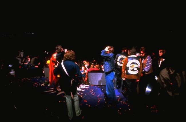 "The Rolling Stones perform at the infamous ""Gimme Shelter"" rock concert at the Altamont Race Track in California on December 8, 1969. A fan was stabbed to death by a member of the Hells Angels motorcycle club, who were hired as bouncers to control the crowd. Hells Angels are on stage with the Rolling Stones' Mick Jagger, wearing red, and guitarist Mick Taylor, with back to camera. (AP Photo)"