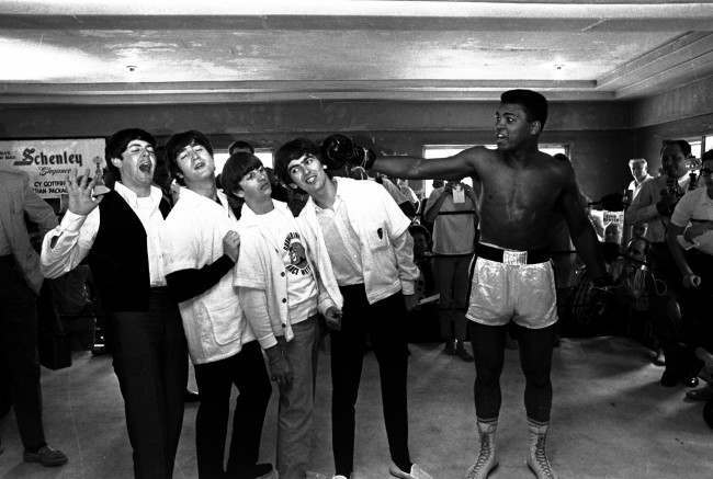 The Beatles, from left, Paul McCartney, John Lennon, Ringo Starr, and George Harrison, take a fake blow from Cassius Clay while visiting the heavyweight contender at his training camp in Miami Beach, Fla. Tuesday February 18,1964.