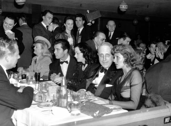 William Randolph Hearst is seen at a Military Ball in Hollywood, Ca. on April 15, 1942. Seated at the table in his row from left to right are: Marion Davies, in uniform, first medical battallion of California State Guard; actor George Montgomery; Hedy Lamarr; Hearst; Rita Hayworth.
