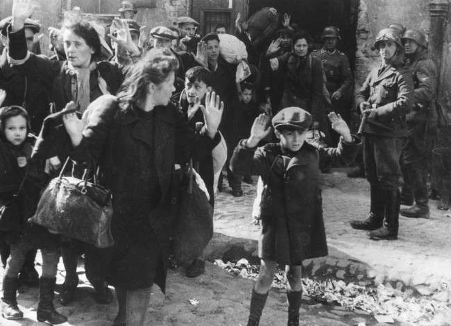A group of Jews, including a small boy, is escorted from the Warsaw Ghetto by German soldiers in this April 19, 1943 file photo. The picture formed part of a report from SS Gen. Stroop to his Commanding Officer, and was introduced as evidence to the War Crimes trials in Nuremberg in 1945. French newspaper Le Figaro reported Saturday May 23, 1998 that Tsvi Nusbaum, a man born in Palestine and now living in New York, may be the boy with his hands up.