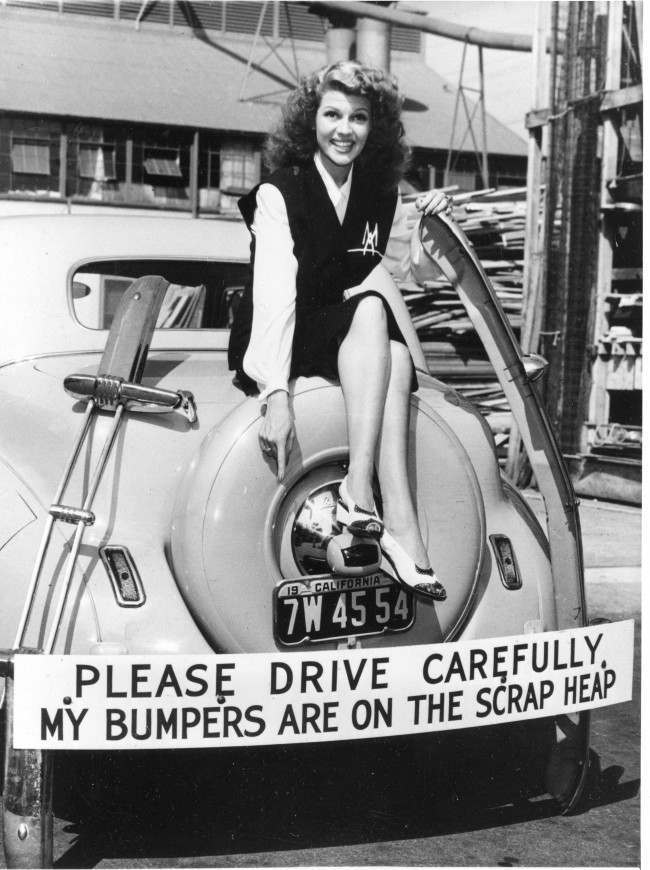 Actress Rita Hayworth participates in the scrap metal recycling campaign by donating her car's bumper in response to the call for bumpers and other non-essential metal car parts for the war effort in Hollywood. Hayworth has also been selling war bonds.