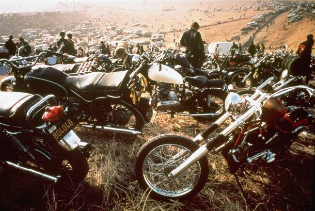 "Motorcycles crowd the field at the infamous ""Gimme Shelter"" rock concert featuring the Rolling Stones."