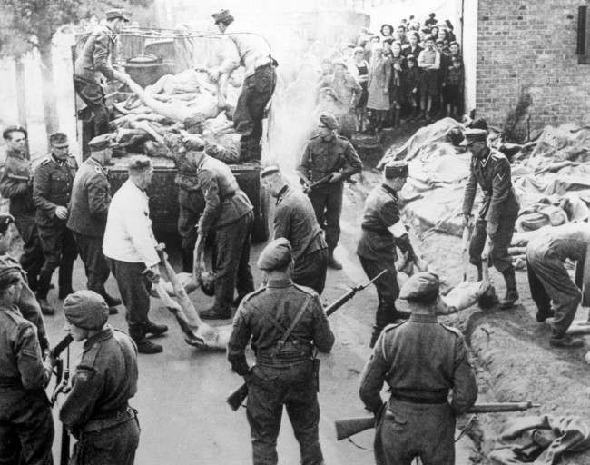 Waffen SS Troops load trucks with bodies under the watchful eye of British and Canadian troops after the concentration camp had been liberated. Date: 16/04/1945
