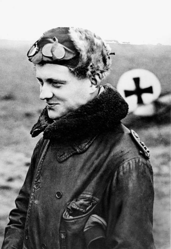 "German airman Manfred von Richthofen, called the ""Red Baron,"" is shown returning from a mission at his squadron's aerodrome at the Front in World War I in 1916. Behind him is the German Cross that marks his plane. (AP Photo)"