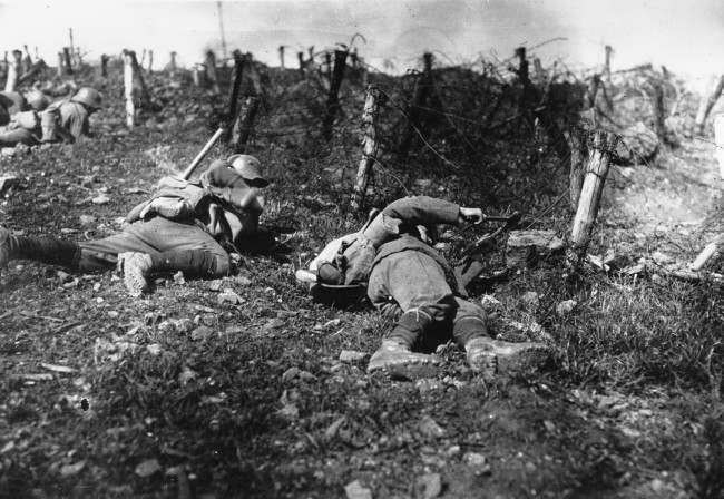 German troops stay close to the ground as one soldier uses pliers to cut barbed-fire fence during World War I. The location is unknown. (AP Photo)