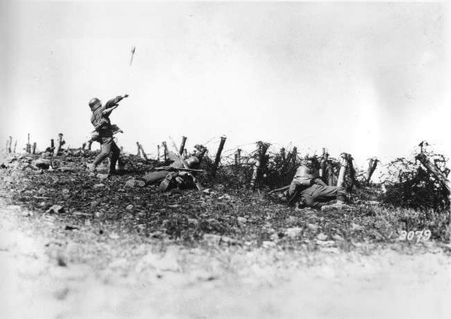 A German soldier throws a hand grenade against enemy positions, at an unknown battlefield during World War I