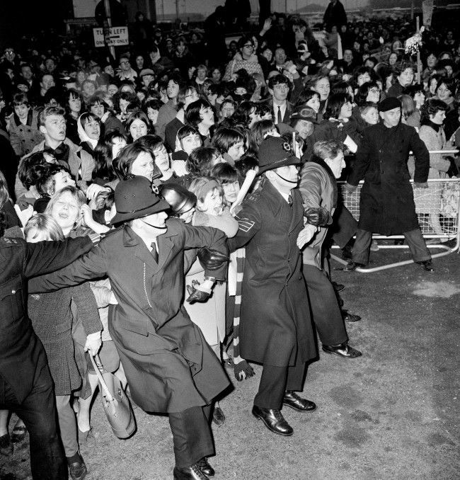 Fans press forward to the restraining linked arms of a chain of extra policemen on duty at London Airport when the Beatles returned from a tour of the United States.