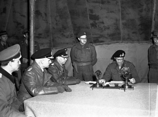 Britain's Field Marshal Bernard Montgomery reads over the surrender pact, while senior German officers, from left, Major Friedel, Rear Admiral Wagner and Admiral Hans-Georg Von Friedeburg, look on, in a tent at Montgomery's 21st Army Group headquarters, at Luneburg Heath, May 4, 1945. The pact agreed a ceasefire on the British fronts in north west Germany, Denmark and Holland as from 8am on May 5. (AP Photo/Eddie Worth)
