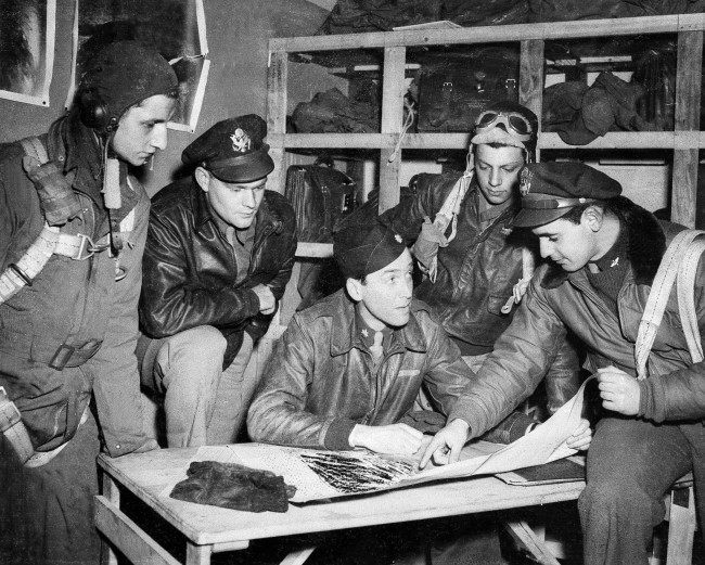 Major Jimmy Stewart talks over the final details of a mission with flyers about to take off, from left to right: Sgt. Keith M. Dibble of Rixford, Pa.; first Lt. Roger Counselman of Meadville, Pa.; Stewart; Sgt. Joseph T. Fiorentino of Philadelphia, Pa.; and second Lt. A.E. Lensky of Monessen, Pa., April 19, 1944, in England during World War II. (AP Photo)