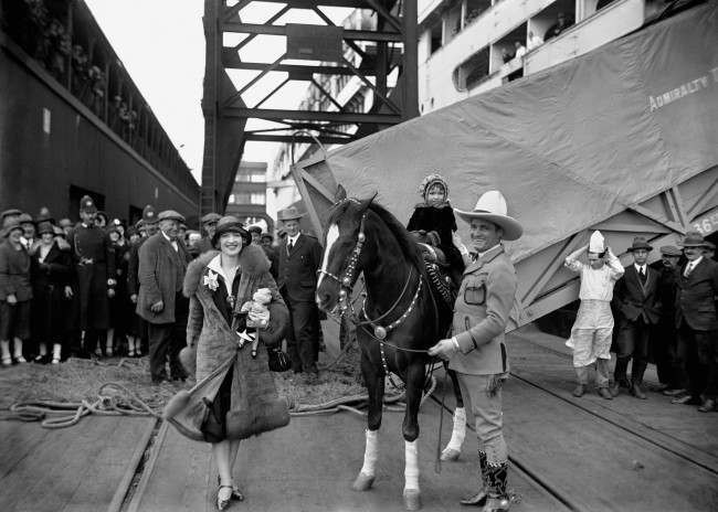 "American ""cowboy"" film star Tom Mix arrives, with his pony, ""Tony"" , his wife actress Victoria Forde and his daughter Thomasina, at Southampton."