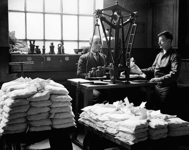 The Royal Mint - London - 1933 Workers weigh the finished coins into bags using the 'automatic weighing machine'.