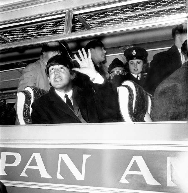 Paul McCartney looks up and acknowledges the waves and screams shortly after arriving with the other three Beatles at London Airport from America.