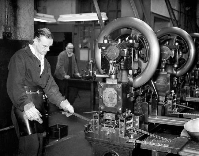 The Royal Mint - London - 1958 Making Gold Sovereigns at the Royal Mint - A man passes strips of gold through the stamping out machine.