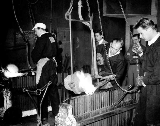 A worker pours molten gold into upright iron moulds - 1958