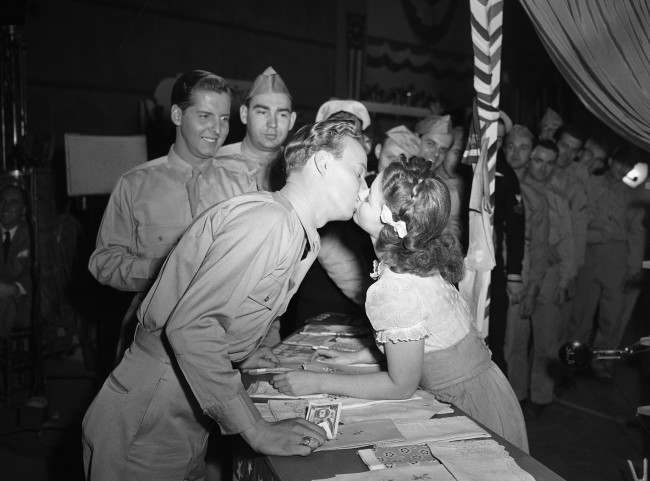 "For the first time in her long movie career, Shirley Temple gets kissed in grown-up fashion by Jerry Shane, an ex-Marine from Grand Rapids, Mich., who plays a bit part in the movie called ""Kiss and Tell,"" Jan. 19, 1945. Some observers at the historical occasion suspected that Shirley's performance was backed by a little previous necking experience, but Shirley wouldn't admit it. (AP Photo/Ira W. Guldner)"