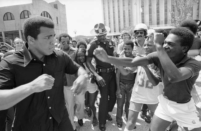 Muhammad Ali, left, playfully spars with a youth on Canal Street in New Orleans, July 31, 1978 where he is promoting his championship fight with Leon Spinks at the Superdome on September 15. Ali took a boat ride, paraded on Canal and then too a turn selling tickets. (AP Photo)