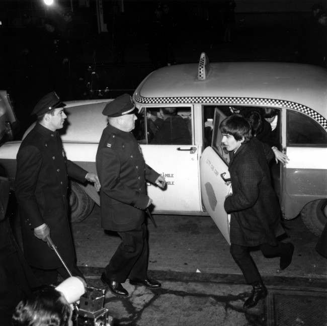 Police security is on hand for the arrival of The Beatles as guitarist George Harrison leads the way from a taxi-cab to Carnegie Hall's stagedoor on W. 56th St. in New York City on Feb. 12, 1964 . About 2,000 fans are gathered outside the concert hall to catch a glimpse of the British rock and roll band on their first U.S. tour. (AP Photo)